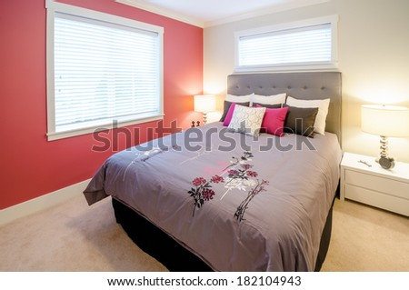 Modern bedroom interior with a red wall, designer pillows, and a floral duvet cover in a luxury house
