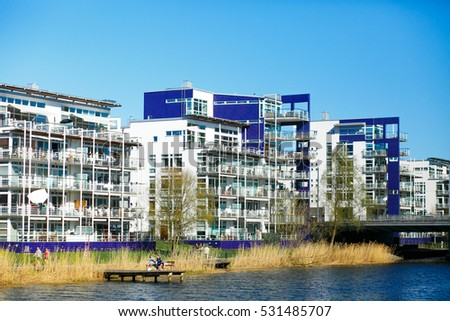 Modern building in blue and white tones stand on the river shore
