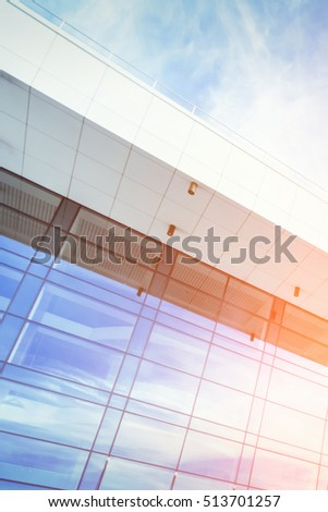 Modern building with a blue glass facade against the sky in the sunlight