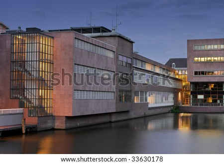 modern building with water surroundings in evening Amsterdam