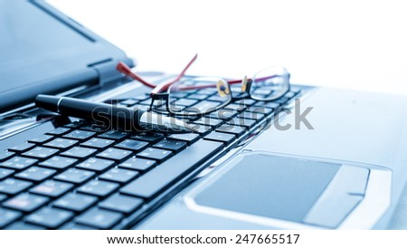 Modern business desk with laptop, pen and glasses. Modern business concepts