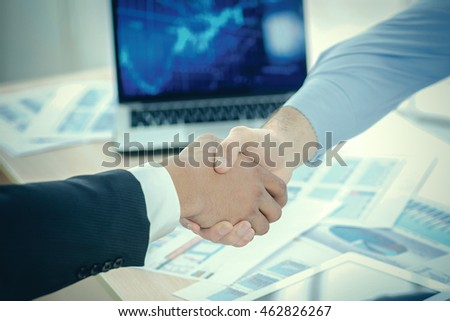 Modern business handshake. Close-up view of a handshake while two successful businessman shaking hands at the table against each in the business office in formal wear and work at a laptop.