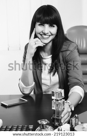 Modern business woman employee of the perfume company. Business lady sitting at a desk. Woman holding a bottle of perfume, offers its customers. Cosmetics, perfumes, sales concept of women's business.