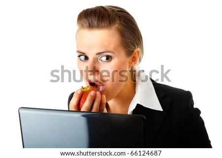 Modern business woman warily looking out from laptop and eating apple