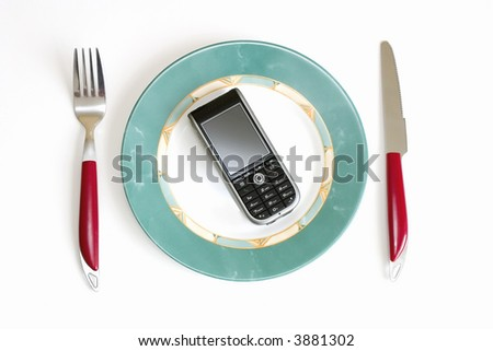 Modern cellular phone (smartphone) on a dish, in surroundings a knife and fork