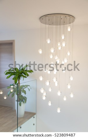 Modern chandelier above staircase in real home