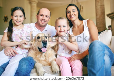 Modern family of father, mother, two daughters and dog posing for camera at home