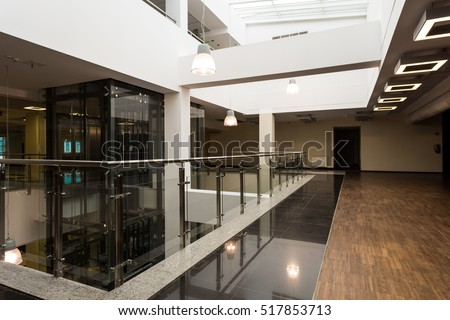 Modern hall with minimalistic ceiling backlight, white pillars, wooden floor and view of glazed lift shaft