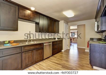 Modern Kitchen Room Interior With Deep Brown Cabinets And Hardwood Floor.  Northwest, USA