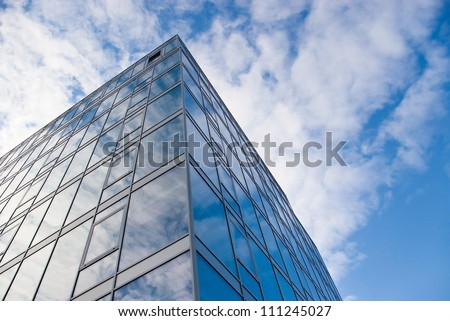 modern office building with glass front and sky reflection