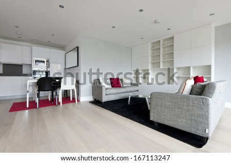 Modern open plan living area with fully fitted kitchen, dining table for four and two large contemporary sofas and glass top coffee table