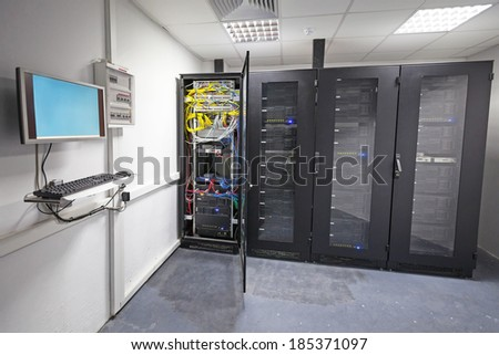 Modern server room interior with black computer cabinets and user terminal on the wall