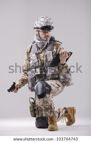 Modern soldier with handgun and tablet computer