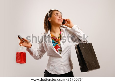Modern woman wearing white jacket talking on the phone and holding shopping bags
