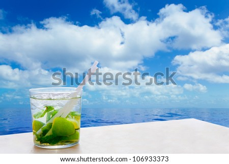Mojito cocktail drink in summer blue calm sea and sky clouds