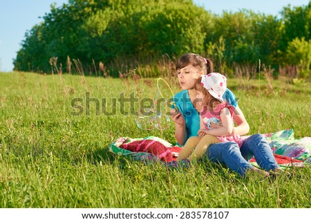 Mom and daughter in the park blow bubbles