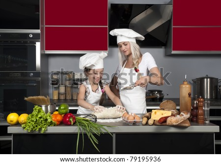 mom teaches daughter to cook in the kitchen at the table with raw food, clothing cooks