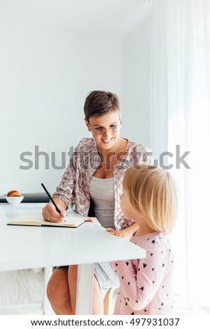 Mom teaching her daughter to write