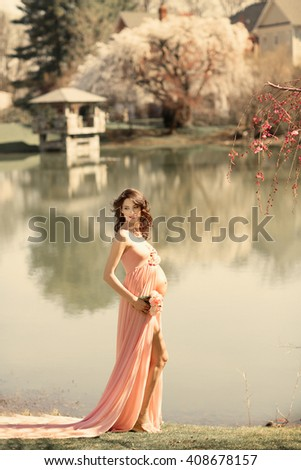mom-to-be in peach gowns near the pond