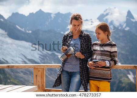 Mom with daughter drinking warm tea in the rustic wooden terrace on mountain, alpine view, snow on hills. Winter weekend. Dombay, Karachay-Cherkessia, Caucasus, Russia.