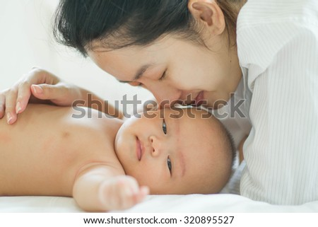 mom with her baby on a white bed