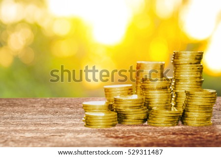 Money coins on wood table with sunrise shining background. New light of hope for good economic concept.