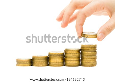 Money concept - hand putting coins on golden money stacks