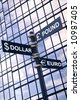 Money concept image of a signpost with Pound, Dollar and Euro against a modern glass office building. - stock photo
