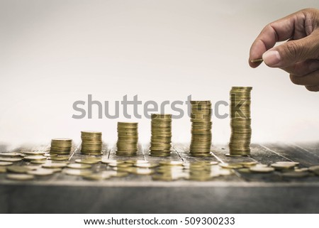 Money, Financial, Business Growth concept, Man's hand put money coins to stack of coins. Hand coins in finger and row stacks them.