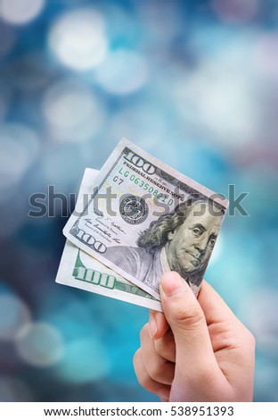Money in hand, isolated on light blue background bokeh