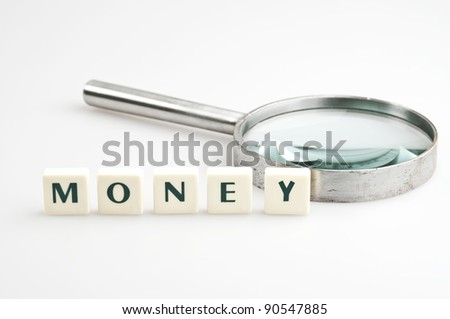 Money word and magnifying glass