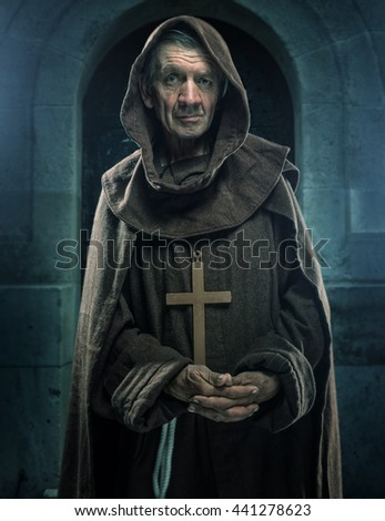Monk holding a wooden cross in front of the old walls