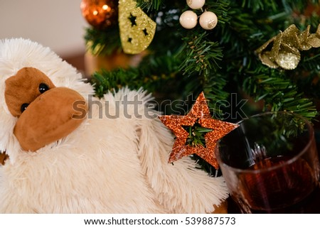 monkey is the symbol of chinese new year   handmade white monkey toy seating on the brown wood table in front of christmas tree with cognac (brandy) in glass