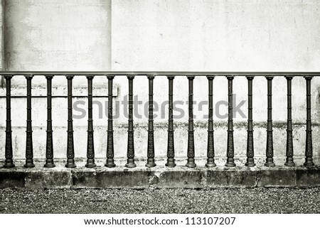 Monochrome image of wrought iron railings against a stone wall