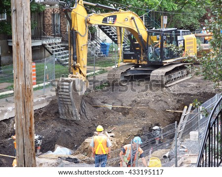 Montreal Quebec Canada  6 June 2016 City road repair and construction workers digging sewer pipes along Verdun residential street .