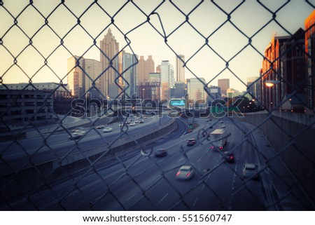 Morning city skyline through the wire mesh fence. Vintage style cityscape background