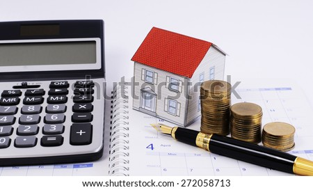Mortgage loans concept with Fountain pen and money coins stack and paper house and calculator on calendar book pages