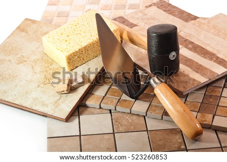 Mosaic tiles, trowel, rubber mallet and a sponge on a white background
