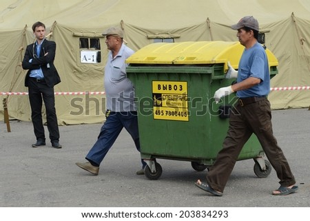 MOSCOW, RUSSIA - AUGUST 1, 2013: Temporary camp for displaced persons contains illegal migrants, discovered during police raids, pending deportation to their homeland. Cleaning dumpsters.