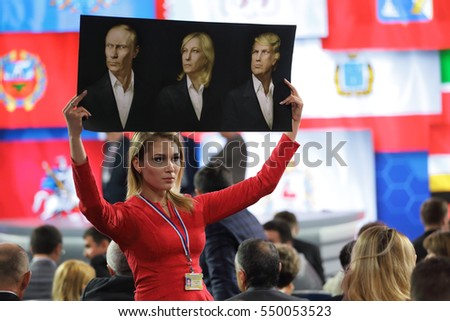 MOSCOW, RUSSIA - DEC 23, 2016: An activist of the NLM Katasonova Maria holds a poster with the image of Vladimir Putin, Marine Le Pen, and Donald Trump at the press conference of the Vladimir Putin
