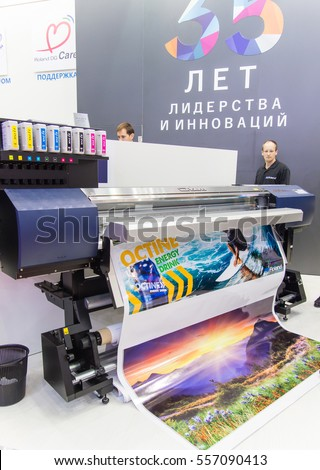 MOSCOW-SEPTEMBER 29, 2016: Business people are watching large format printer brand Roland at the International Trade Fair Advertising