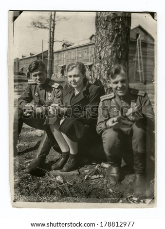 "MOSCOW, USSR - CIRCA 1950s : An antique photo shows Soviet Army soldiers and their girlfriend under the tree. ""Soviet people"" series."