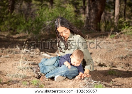 Mother and baby boy studying things in nature