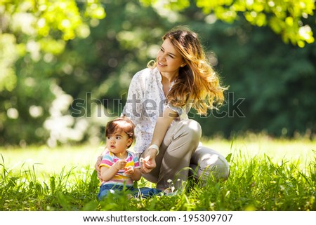 Mother and baby girl sitting and relaxing in park.