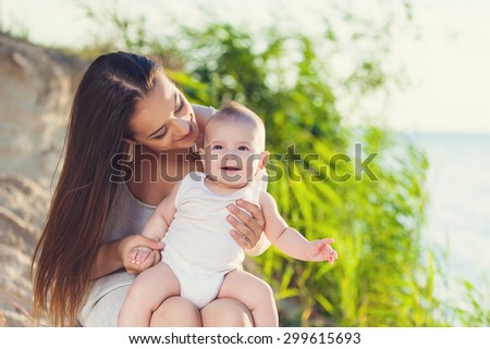 mother and baby having fun at the beach