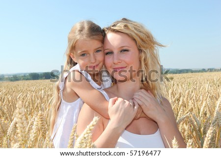 Mother and child in wheat field on sunny day