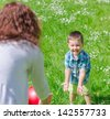 Mother and child playing with the ball outdoors - stock photo