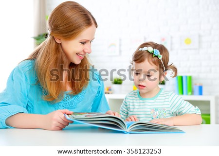 mother and child reading a book together at home