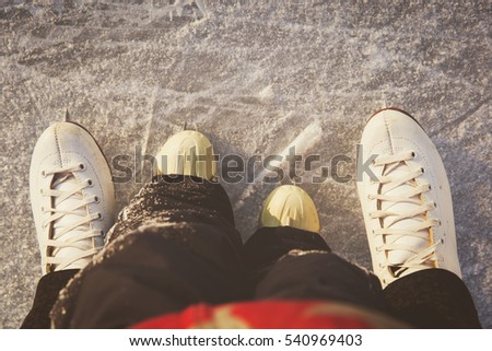 mother and child skating together in winter
