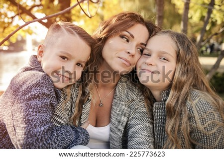 Mother and children in autumn park under a tree.